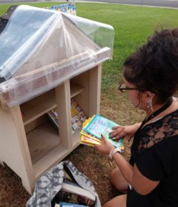 Flor Puts books into Little Library