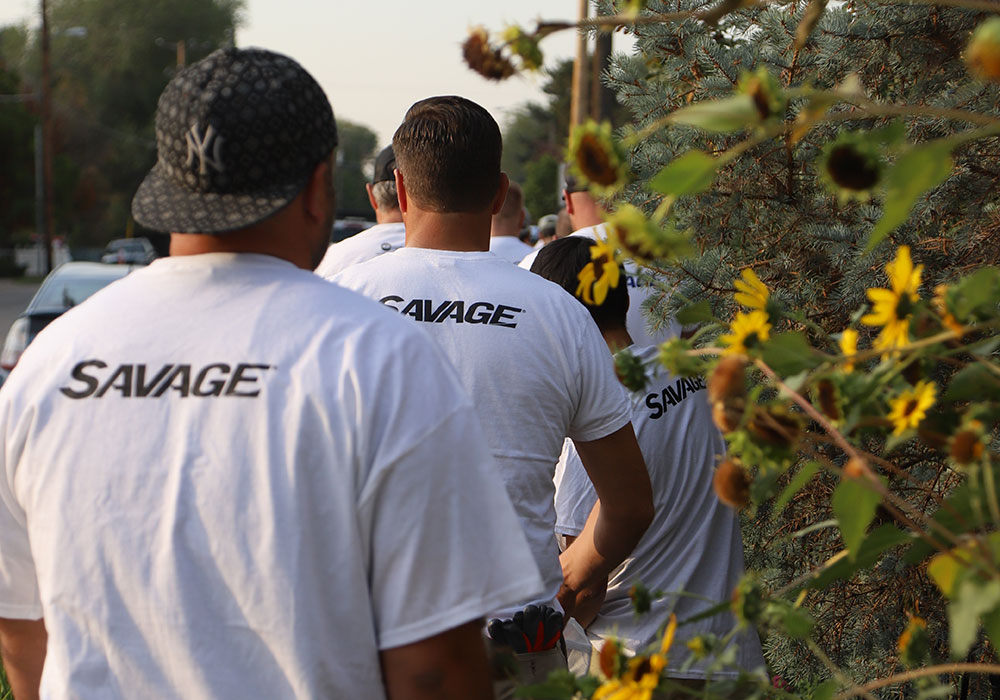 Volunteers from Savage walk by sunflowers at Monarch Park