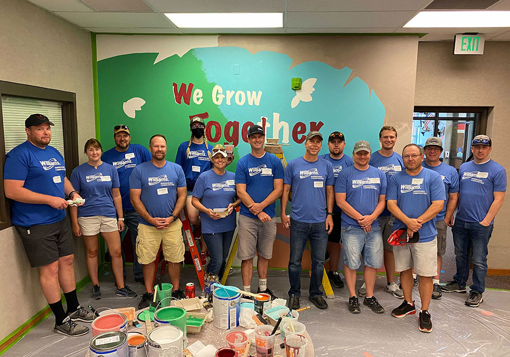 Williams Volunteers Stand in front of painting they did for Day of Caring